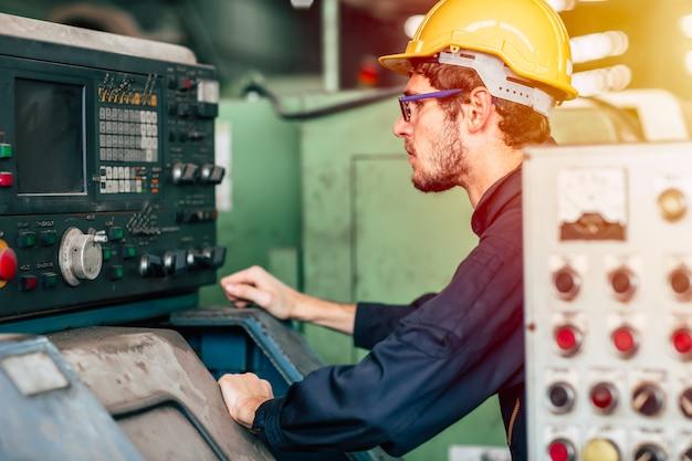 Engenheiro técnico de profissão jovem operar máquina pesada para cnc automatizado na fábrica.