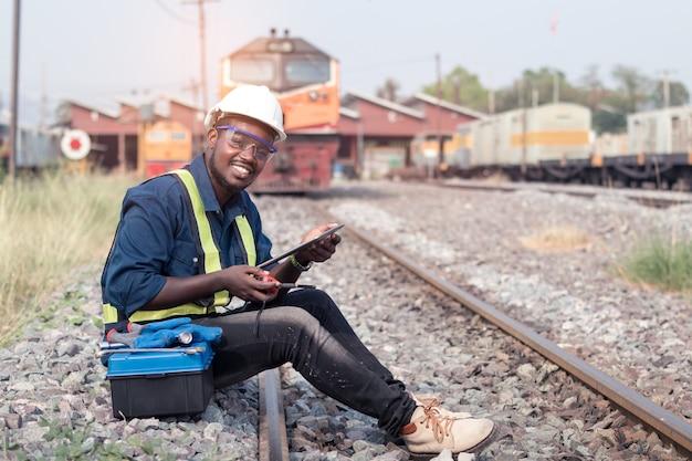 Engenheiro técnico homem africano verifica e repara o trem na ferrovia segurando um tablet e falando por comunicação de rádio ou walkie talkie