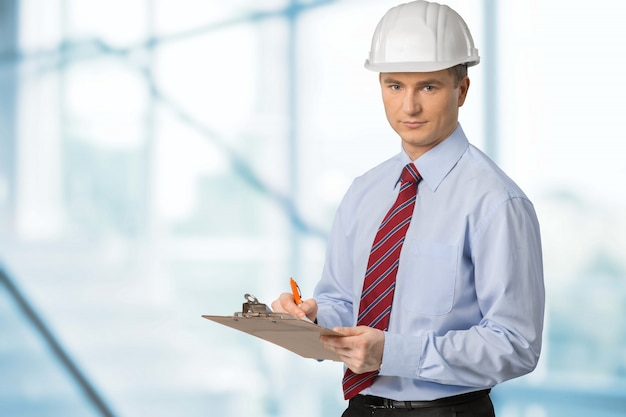 Engenheiro tomando nota. homem focado no capacete de segurança branco segurando uma prancheta e escrevendo.