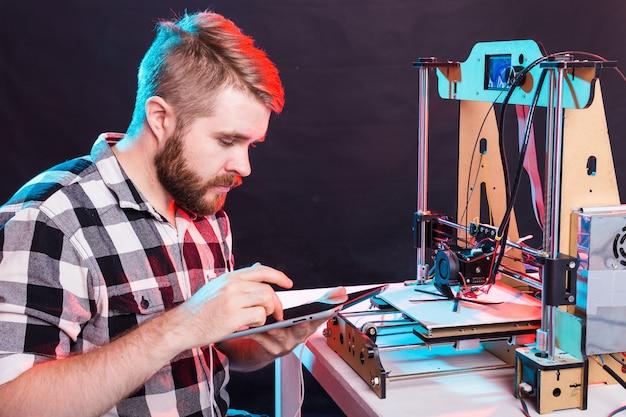 Engenheiro trabalhando à noite no laboratório, ele está ajustando os componentes da impressora.
