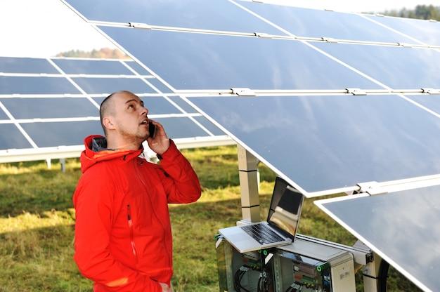 Engenheiro trabalhando com laptop por painéis solares, falando no celular
