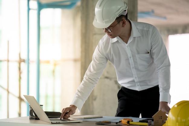 Engenheiro trabalhando com laptop sobre o plano de construção no local