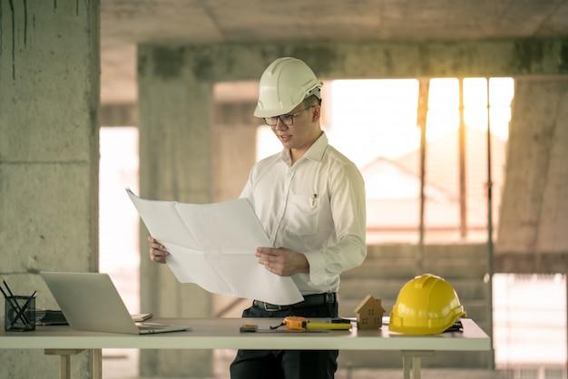 Engenheiro, trabalhando com o computador portátil sobre o plano de construção no local