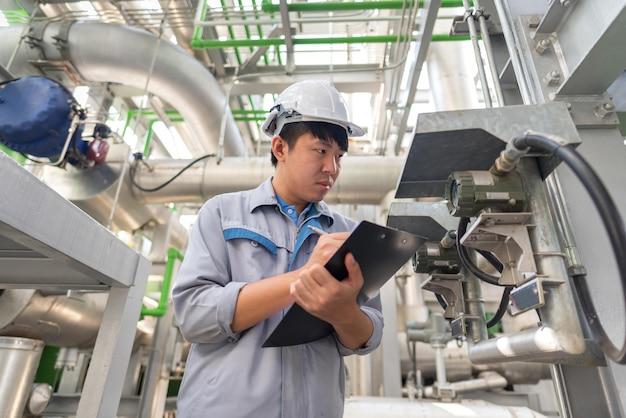 Engenheiro trabalhando e válvula de retenção na fábrica de usina termelétrica