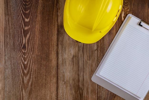 Engenheiro, trabalhando na mesa de escritório com capacete de segurança amarelo protetor de construção de caderno em branco sobre fundo de mesa de madeira
