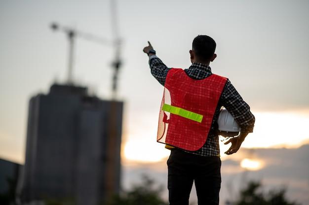 Engenheiro trabalhando no canteiro de obras na hora do pôr do sol da silhueta