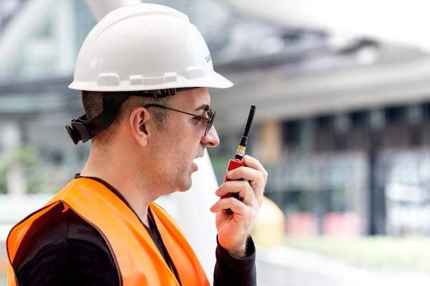 Engenheiro usa capacetes brancos e roupa de segurança está falando no rádio com o colega fora
