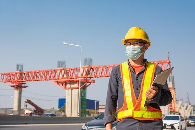 Engenheiro usa máscara para trabalhar na construção de estradas
