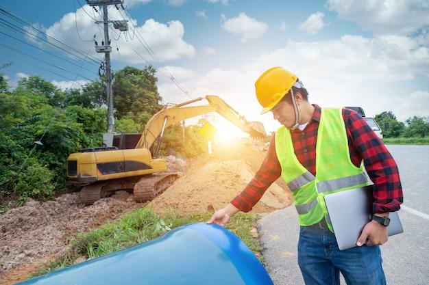 Engenheiro usa uniforme de segurança segurando um laptop examinando a escavação do grande remendo do tubo