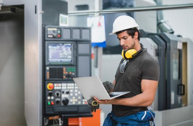 Engenheiro usando computador portátil controle operacional máquinas na fábrica