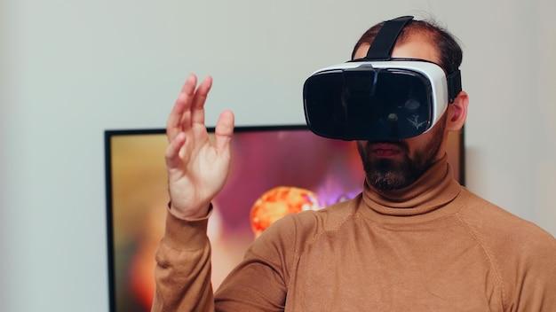 Engenheiro usando fone de ouvido de realidade virtual no escritório doméstico para desenvolver tecnologia de engrenagens moderna.