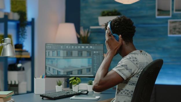 Engenheiro usando fones de ouvido e projetando o modelo de construção
