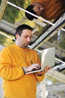 Engenheiro usando laptop e conectando os fios no local de trabalho