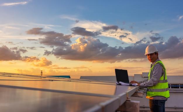 Engenheiro usando laptop em painéis solares no telhado no céu do sol, um engenheiro que trabalha em uma fazenda fotovoltaica. eco tecnologia para energia elétrica