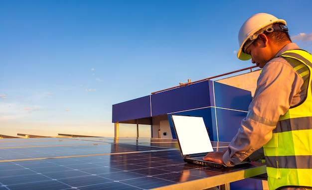 Engenheiro usando laptop em painéis solares no telhado no pôr do sol céu engenheiro trabalhando em uma fotovoltaica