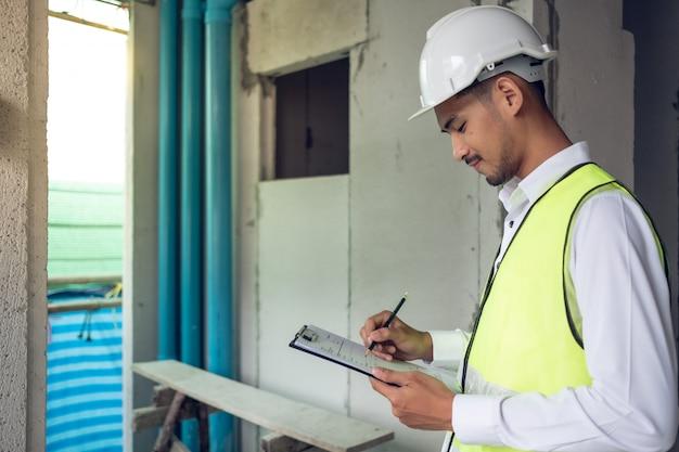Engenheiro, verificação de defeito no canteiro de obras sobre a linha de solo e resíduos de tubos de pvc