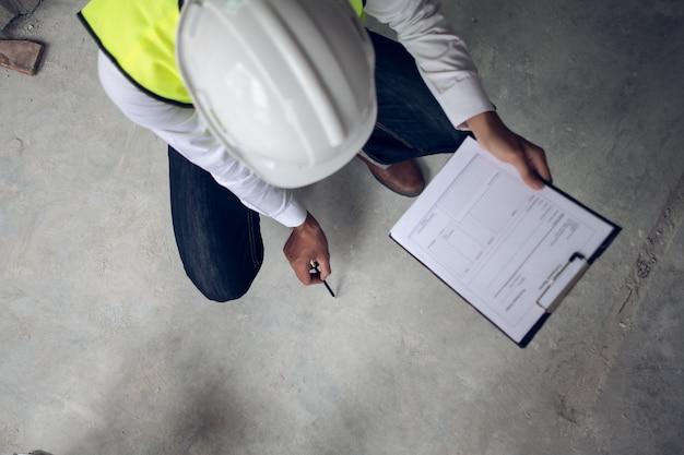 Engenheiro, verificação de defeito no canteiro de obras sobre a superfície do piso de concreto