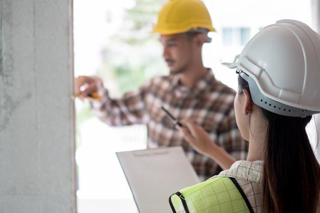 Engenheiro, verificando o defeito no canteiro de obras, medindo a dimensão correta da coluna de concreto