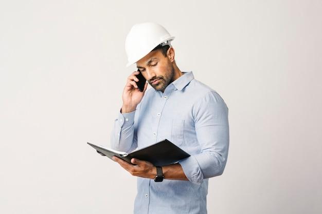 Engenheiro verificando seu planejador enquanto fala ao telefone
