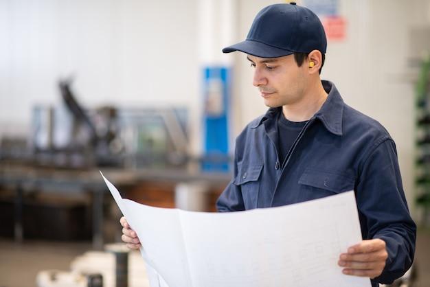 Engenheiro vestido de azul lendo um desenho de bluepring em uma instalação industrial
