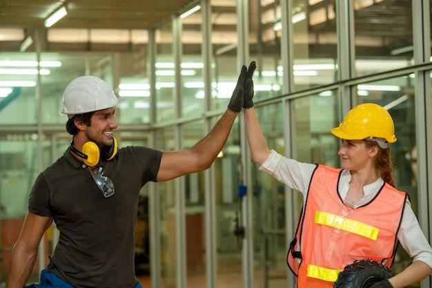 Engenheiro, vestindo uniforme de pé de segurança e coordenação da mão com ação feliz para o trabalho em equipe na fábrica