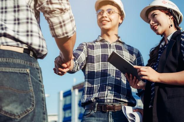 Engenheiros apertam as mãos junto com a garota da secretária ao lado.