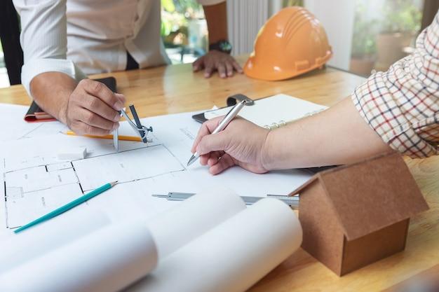 Engenheiros arquitetos e equipe do escritório agente imobiliário trabalhando com plantas