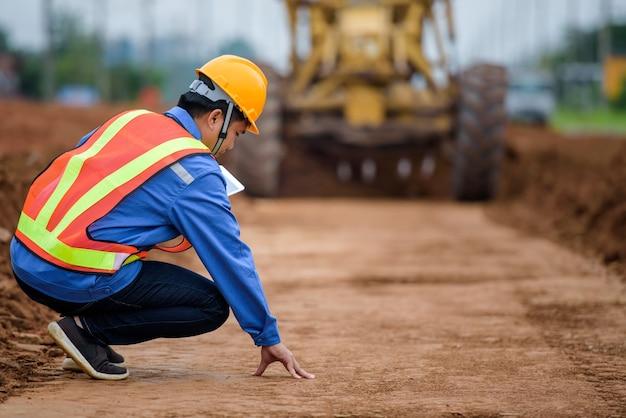 Engenheiros asiáticos observam a reconstrução da estrada e inspecionam a construção da estrada no local de construção.