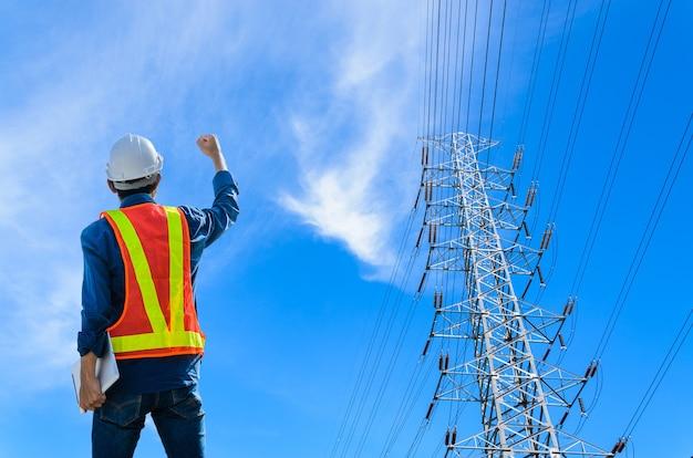Engenheiros bem-sucedidos enfrentam postes de alta tensão em um fundo azul.