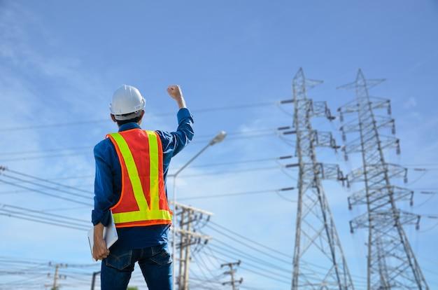 Engenheiros bem-sucedidos se posicionam contra o poste de energia no fundo azul.