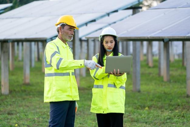 Engenheiros com arquitetos examinando usinas de energia solar.