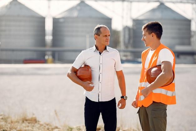 Engenheiros com capacetes em pé na fábrica