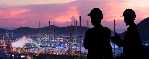 Engenheiros da silhouette estão de pé a indústria de refino de petróleo