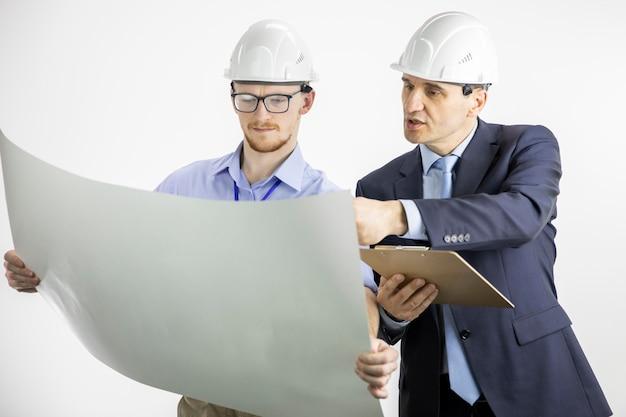 Engenheiros de arquitetura, trabalhando com documentos de planta na parede branca