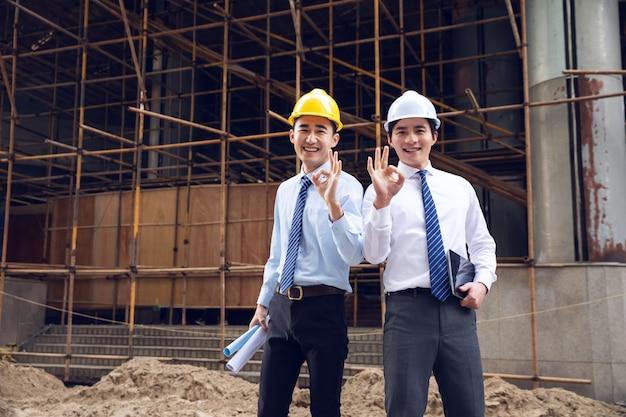Engenheiros de capacetes ao lado da fábrica