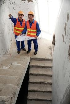 Engenheiros de construção discutindo problema sério com a unidade de escada que foi instalada incorretamente