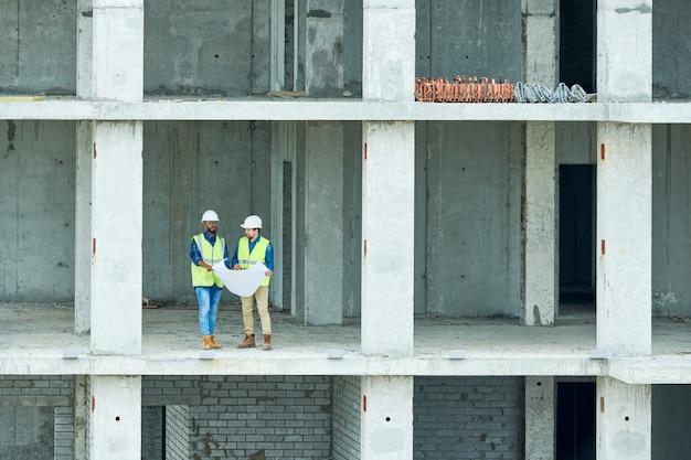 Engenheiros de construção lendo rascunho em edifício inacabado