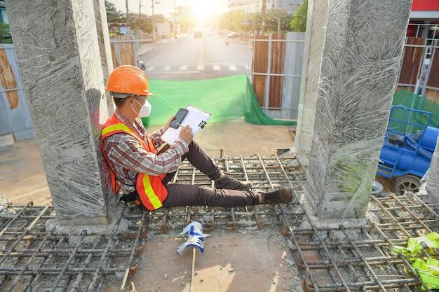Engenheiros de construção, supervisionando o andamento do projeto de construção, ficam na nova fábrica, engenharia, consultoria, pessoas no canteiro de obras, segurando a planta na mão.
