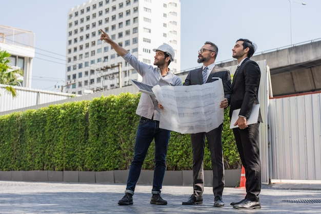 Engenheiros de energia discutindo com dois empresários e apontando para o local de instalação do painel solar de energia nas plantas do edifício