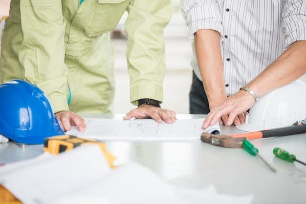 Engenheiros de equipe e contramestre discutem no canteiro de obras