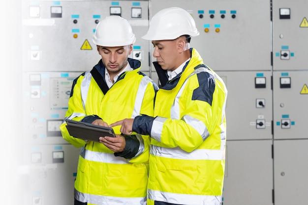 Engenheiros de jovens trabalhadores usando capacete e uniforme de proteção enquanto trabalham com uma máquina de alta tecnologia