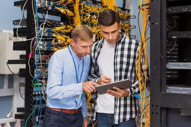 Engenheiros de rede com um tablet tiro médio