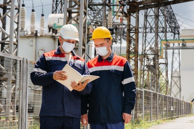 Engenheiros de subestações elétricas realizam um levantamento dos modernos equipamentos de alta tensão na máscara no momento da pandemia. energia. indústria.