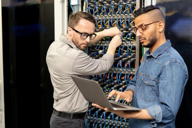Engenheiros de ti multiétnicos configurando cluster de computadores