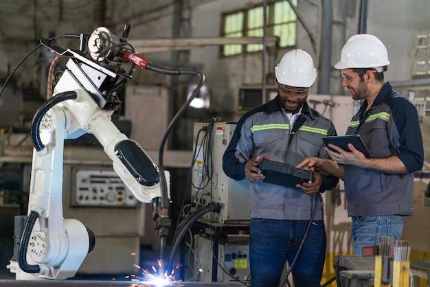 Engenheiros do sexo masculino controlam a máquina do braço do robô soldando aço com controle remoto e tablet na fábrica