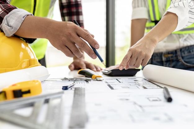 Engenheiros e arquitetos apontando as plantas da casa projetadas para o cliente, encontrando ambiente, se reúnem para planejar a construção e consertá-la. idéias de design e design de interiores.