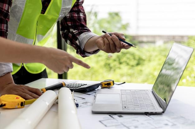 Engenheiros e arquitetos apontando para telas de laptop olhando projetos para fazer algumas modificações, eles se reúnem para planejar a construção e os consertos. idéias de design e design de interiores.