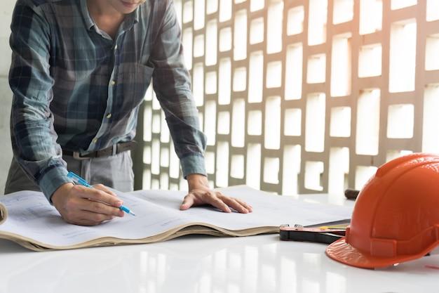 Engenheiros e capacetes de segurança explicam plano de construção olhando drawin de papel de modelo