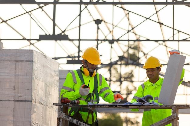 Engenheiros e consultores asiáticos calculam a quantidade de tijolos usados na construção, conceito de trabalho em equipe de construção.