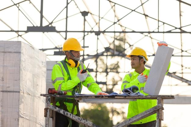 Engenheiros e consultores asiáticos calculam a quantidade de tijolos usados na construção de fundo é a estrutura do telhado, conceito de trabalho em equipe de construção.